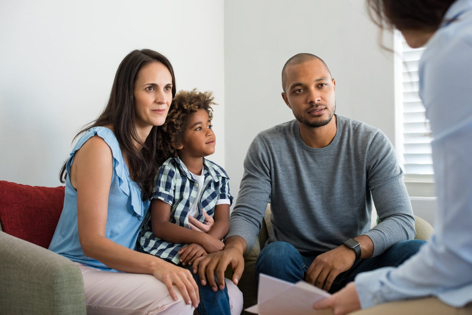 Serious couple with son in a deep conversation with family counselor. Multiethnic parents talking about adoption with their counselor. Family at the financial planning consultation.